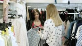 harcamak : Two happy young girls are choosing clothes in a department store. 4K