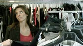 wieszak : Two happy young girls are choosing clothes in a department store. 4K