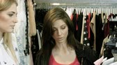 hanger : Two happy young girls are choosing clothes in a department store. 4K