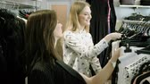 two : Two happy young girls are choosing clothes in a department store. 4K