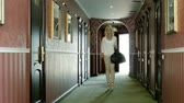 llegando : Beautiful young blond woman walking through the hall of luxury hotel. HD