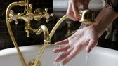 fikstür : The woman filling the bathtub with water and womens hand trying water. Slow motion. HD Stok Video