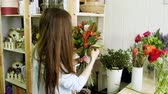 retailer : Female florist in flower shop. Woman making a beautiful and stylish bouquet of fresh flowers in floral design studio. 4K Stock Footage