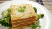 cheese sauce : Italian food. Close-up shot of meat lasagna on a white plate. Slow motion. HD