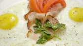 omelete : English breakfast. Close-up shot of three fried eggs and bacon serving on a white plate. Slow motion. HD