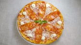 salam : Italian food. Top view of delicious pizza with tomato sauce, salami slicing, fresh basil leaves, parmesan and cream cheese, red onion served on a round white plate. Slow motion. HD Stok Video