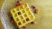 belga : Sweet breakfast. Top view of viennese waffles with fresh berries, honey, syrup on a glass plate. 4K