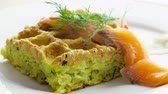 agrio : Potato casserole. Close-up shot of pudding in shape of waffles with fresh cucumber, tomato, dill, smoked salmon, sour cream on the white plate. 4K Archivo de Video
