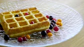 wafers : Sweet breakfast. Close-up shot of viennese waffles with fresh berries, honey, syrup on a glass plate. 4K Stock Footage