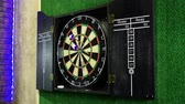flechette : Close-up shot of dart arrow hitting in target center of dartboard in game of darts. 4K Vidéos Libres De Droits