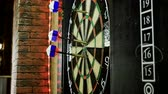 ダーツ : Close-up shot of dart arrow hitting in target center of dartboard in game of darts. 4K 動画素材