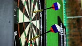 ブルズアイ : Close-up shot of dart arrow hitting in target center of dartboard in game of darts. 4K 動画素材
