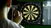 ブルズアイ : Man throwing a dart arrow in target center of dartboard in game of darts. 4K 動画素材