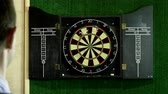 дартс : Man throwing a dart arrow in target center of dartboard in game of darts. 4K Стоковые видеозаписи