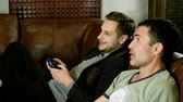 sofa : Two men sitting on a leather couch, holding gamepad with both hands and having fun playing video game on console. 4K Stock Footage