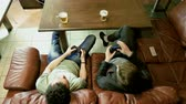 развлекать : Two men sitting on a leather couch, holding gamepad with both hands and having fun playing video game on console. 4K Стоковые видеозаписи