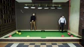 biliardo : Two men playing billiards, hitting balls with legs, kicking it into holes on a floor billiard table. 4K Filmati Stock