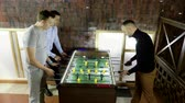 крикет : Sport, game concept. Foosball. Three men playing a table football or kicker with miniature players. 4K