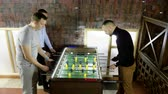críquete : Sport, game concept. Foosball. Three men playing a table football or kicker with miniature players. 4K