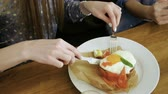 forchetta : Close-up shot of woman eating an english breakfast: poached egg, smoked salmon, red caviar, spinach leaves on toast bread. 4K