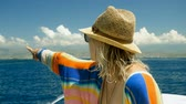 strohhut : A young woman sailing at luxury boat and pointing in the direction of the Mediterranean sea. Slow motion. HD Stock Footage