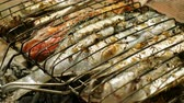 empoleirar : Mackerel, perch, sea bass, dorado, mullet, tuna. Close-up shot of fish grilled over charcoal. 4K