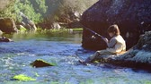 fishing reel : Boy fishing by the river Stock Footage