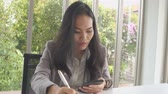 Asian business female working with smartphone and review document at office building