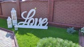 cohesion : Love word outdoors. Big white plastic letters wedding decoration Stock Footage