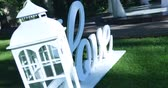 cohesion : Love word outdoors. Big white plastic letters on the grass near green fir trees in the garden, wedding ceremony decoration, romantic holiday decor Stock Footage
