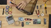 start over : A man disassemble a laptop with a screwdriver. Wooden table top view.