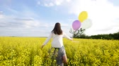tot : Girl with balloons on the shoulders of the guy runing in field rape Stock Footage