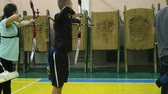 atirador : 17.10.2017 - Chernivtsi, Ukraine. Hands of young person holding bow and arrow, trainer explains shooting method