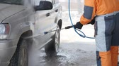 hadice : worker wash car strong streams of water winter