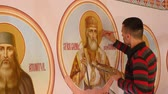 концентрация : 30.01.2018, Chernivtsi, Ukraine - Male Artist is Standing and painting the Icon of Orthodox Saint , Holding a Palette With Paints