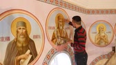 католицизм : 30.01.2018, Chernivtsi, Ukraine - Male Artist is Standing and painting the Icon of Orthodox Saint , Holding a Palette With Paints