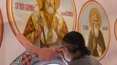 30.01.2018, Chernivtsi, Ukraine - Male Artist is Standing and painting the Icon of Orthodox Saint , Holding a Palette With Paints