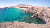 ランサローテ : Pan at playas papagayos in lanzarote showing people swimming and boats in the ocean.
