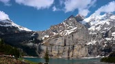 world heritage site : Lake Oeschinen with snowy mountains and clouds - time lapse