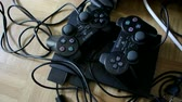 play video game : LONDON, UNITED KINGDOM - NOVEMBER 8, 2014:  Panning over of a Sony Playstation joysticks controller and console device full of dust on a wooden floor