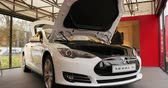 admirado : PARIS, FRANCE - 28 NOVEMBER 2014: White electric car, Tesla Model S 85 inside the showroom admired by future customers. Tesla Motors, Inc. is an American company that designs, manufactures, and sells electric cars and electric vehicle powertrain component
