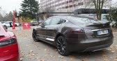 tesla motors : PARIS FRANCE  CIRCA 2015: Panning to metallic grey Tesla Model S at  showroom. Tesla is an American company that designs manufactures and sells electric cars