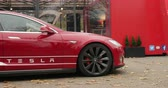 tesla motors : PARIS, FRANCE - CIRCA 2015: Left panning to Red Tesla Model S hybrid car in front of showroom. Tesla is an American company that designs, manufactures, and sells electric cars