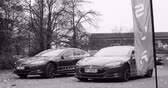 fábrica : PARIS, FRANCE - CIRCA 2015: Two Tesla Hybrid in front of showroom - black and white. Tesla is an American company that designs, manufactures, and sells electric cars Vídeos