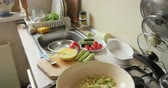 cutting in : Woman cooking preparing delicious food in the kitchen - slicing cucumber than mixing the bell pepper and zucchini on hot pan on gas stove Stock Footage