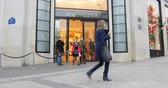must see : PARIS, FRANCE - CIRCA 2016 Street view of Louis Vuitton flagship store on the Champs-Elysees Nr 101 in Paris, France with pedestrians admiring the store, customers entering and exit with shopping bags