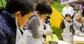 przetwory : PARIS, FRANCE - FEB 2016: Kids being food-chefs at the Bonduelle stand - Agricultural Show - Salon International de Agriculture. Bonduelle is a conglomerate with produce diverse fruits and vegetables products Wideo