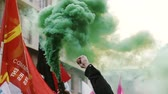 valls macrom : STRASBOURG, FRANCE - 9 MAR 2016: Man holding green smoke grenade flares  as thousands of people demonstrate as part of nationwide day of protest against proposed labor reforms by Socialist Government