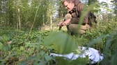 pokrzywa : Side view of happy man pickling wild garlic in green forest