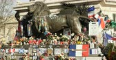 egalite : PARIS, FRANCE - CIRCA 2015: Lion statue at the Monument a la Republique surrounded with placards and signs and flags after Paris attacks at Bataclan Theater